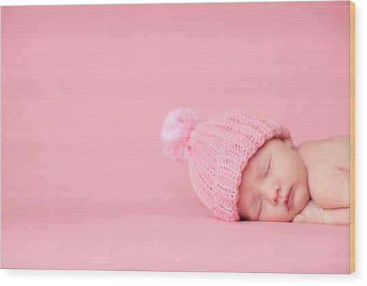 Newborn Baby Girl Sleeping Peacefully On Pink Background Wood Print by Ideabug