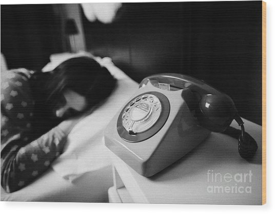Old Fashioned Gpo Bt Phone On Bedside Table Of Early Twenties Woman In Bed In A Bedroom Wood Print by Joe Fox