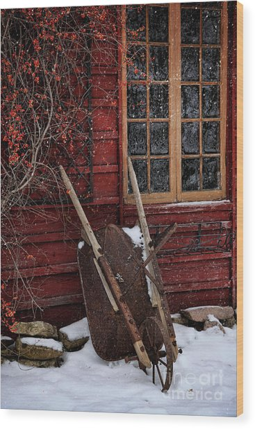 Old Wheelbarrow Leaning Against Barn In Winter Wood Print