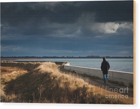 One Man Walking Alone By Sea Wall In Sunshine On Dramatic Stormy Wood Print