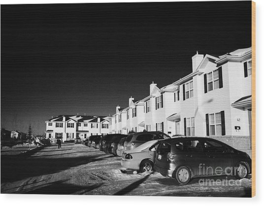 outdoor parking lot with vehicles outside row of condominium starter homes during winter Saskatoon S Wood Print