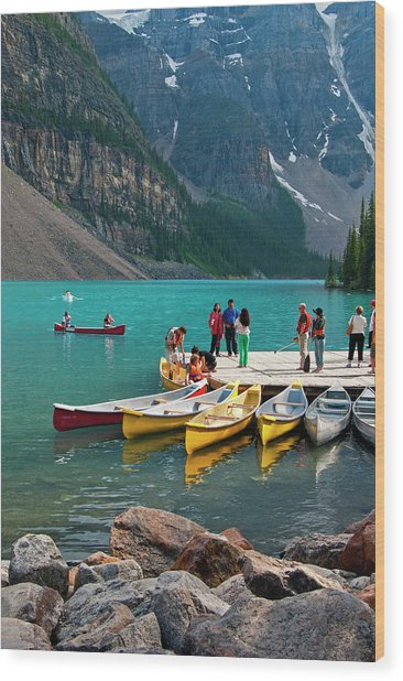 Passengers Renting Colourful Canoes On Wood Print by Emily Riddell