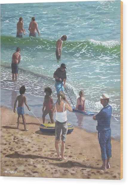 people on Bournemouth beach pulling dingys Wood Print