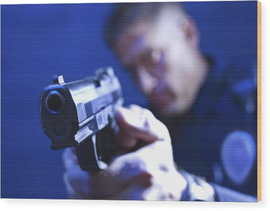 Police Officer Aiming Gun Wood Print by Jupiterimages