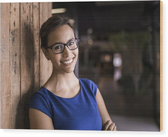 Portrait Of Confident Businesswoman Against Wooden Wall Wood Print by Portra