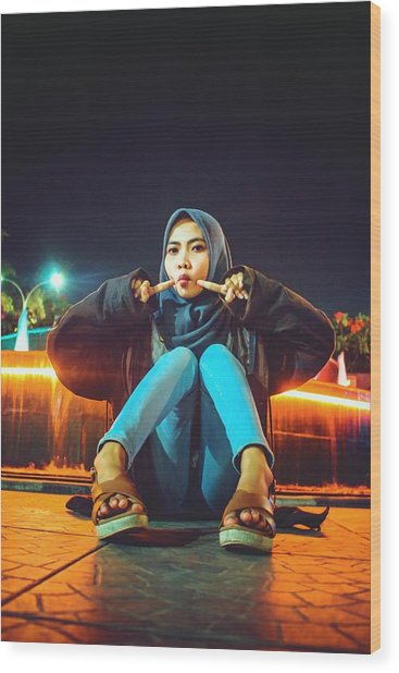 Portrait Of Young Woman Wearing Hijab While Sitting On Footpath At Night Wood Print by Ilham Adhi Kusuma / EyeEm
