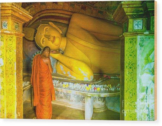 praying buddhist monk by a lying buddha in Sri Lanka Wood Print by Gina Koch