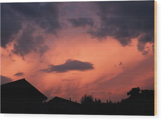 Purple Clouds Gather In A Pink Sky Above Dark Houses Wood Print by Photodisc