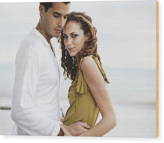 Romantic Couple Standing Together, Woman Looking At Camera Wood Print by Digital Vision.