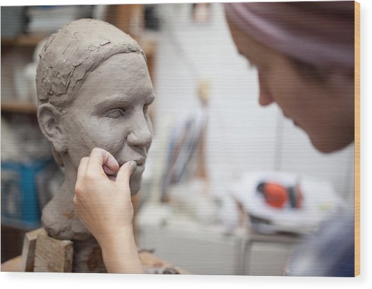 Sculptor Working On Head Sculpture Wood Print by Guido Mieth