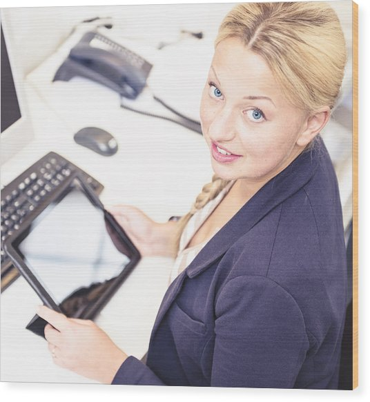 Secretary In Her Office Using A Digital Tablet Wood Print by Franckreporter