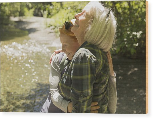 Senior Woman And Daughter Hiking Hugging By River Wood Print by Compassionate Eye Foundation/Steven Errico