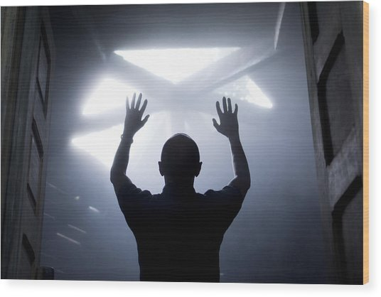 Silhouette Of A Man With Raised Hands Against Light Coming From Above. Wood Print by Maciej Toporowicz, NYC