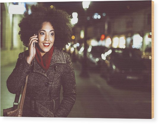 Smiling Young Woman Using Phone On Street By Night Wood Print by Portishead1