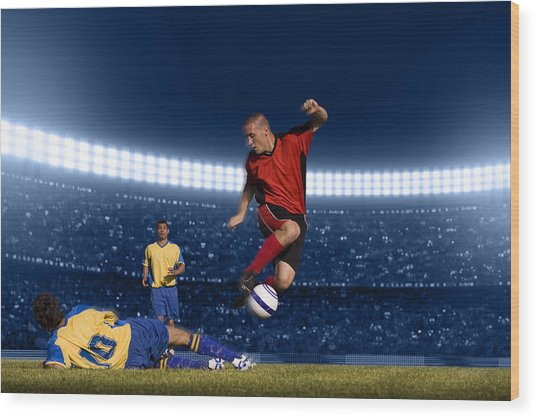 Soccer Player Jumping With Ball Wood Print by Kycstudio