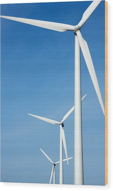 Three Mighty Windmills In A Row Against A Blue Sky. Wood Print
