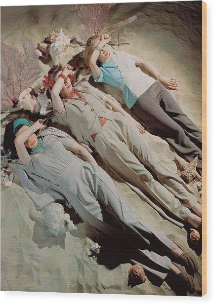 Three Models Lying Down On Sand Wood Print by John Rawlings
