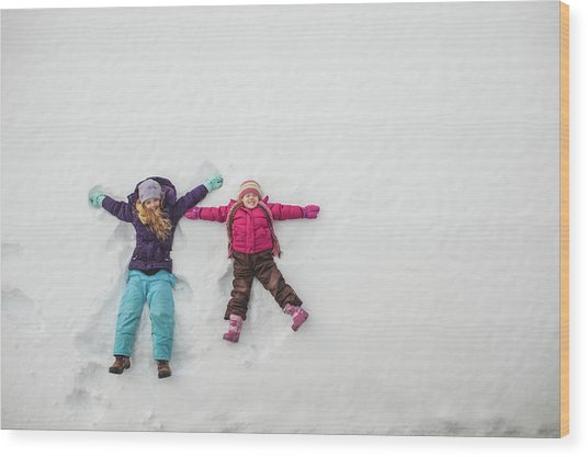 Two Sisters Playing, Making Snow Angels Wood Print by Hugh Whitaker