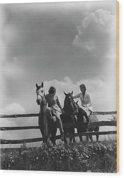 Two Women Sitting On A Fence With Horses Wood Print