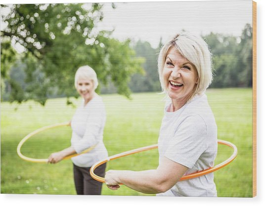 Two Women With Plastic Hoops Wood Print by Science Photo Library
