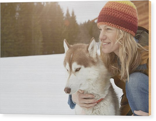 Woman Kneeling With Husky In Snow Covered Landscape, Elmau, Bavaria, Germany Wood Print by Stephen Lux