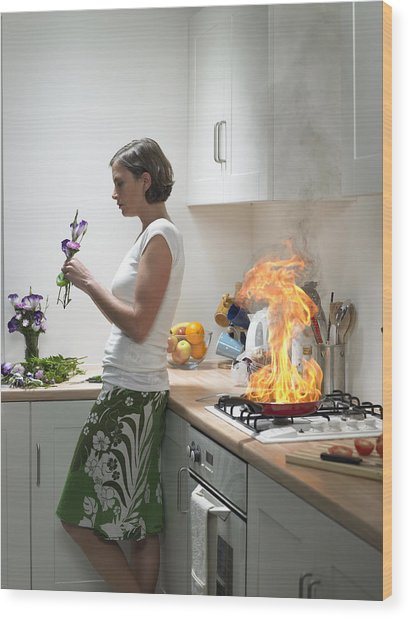 woman Leaning Against Kitchen Worktop Holding Flower, Frying Pan On Fire Behind Wood Print by Michael Blann