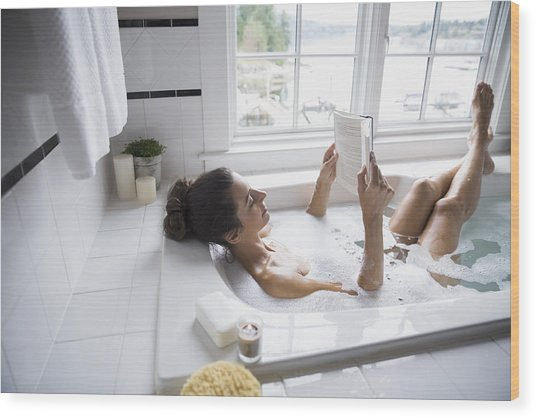 Woman Reading Book In Bubble Bath Wood Print by Hero Images