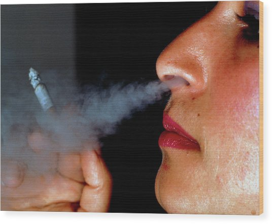 Woman Smoking A Cigarette Wood Print by Harvey Pincis/science Photo Library