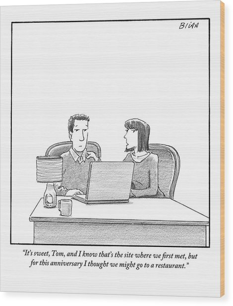 Woman Speaks To Husband As They Sit Behind A Desk Wood Print