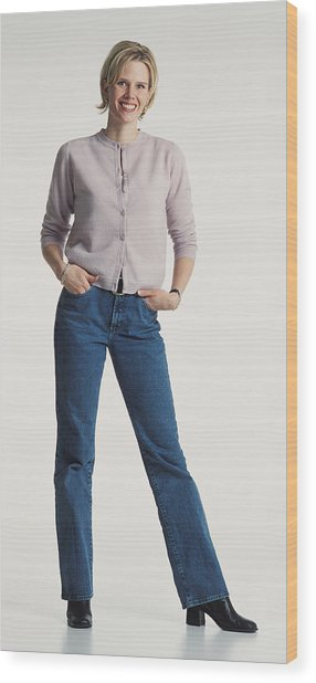 Young Beautiful Caucasion Adult Female Dressed Casually In Jeans And A Sweater Stands Smiling Confidently At The Camera Wood Print by Photodisc