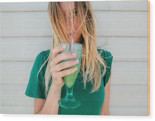 Young Blond Woman In A Green Top, Drinking Juice Wood Print by Matilda Delves