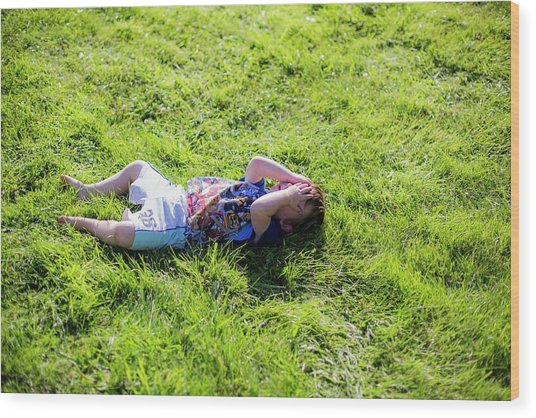 Young Boy Lying On Grass Wood Print by Samuel Ashfield