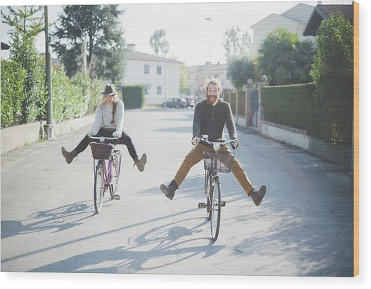 Young Couple Cycling With Legs Out Wood Print by Eugenio Marongiu