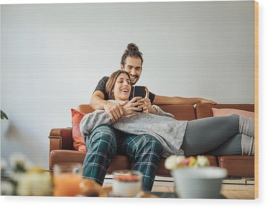 Young Couple With Smart Phone Relaxing On Sofa Wood Print by Luis Alvarez