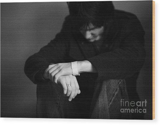 Young Dark Haired Teenage Man Sitting On The Floor With Back Against The Wall In The Fetal Position  Wood Print by Joe Fox