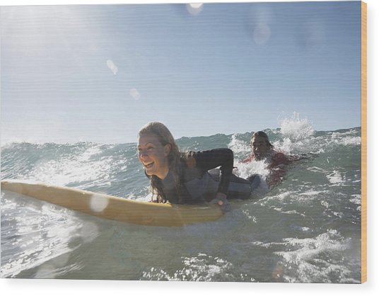 Young Man Being Towed In Sea By Young Woman On Surfboard, Smiling Wood Print by Anthony Ong