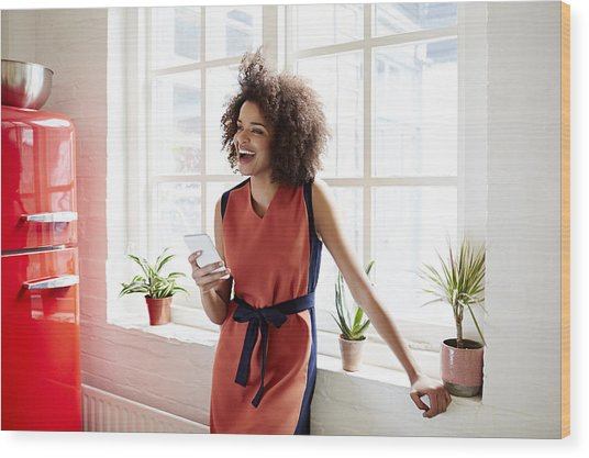 Young Woman Laughing In A Trendy Apartment Wood Print by Ezra Bailey