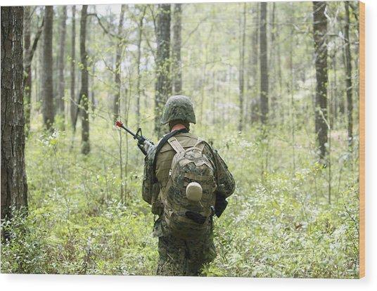 A U.s. Marine Patrols Through A Forest Wood Print