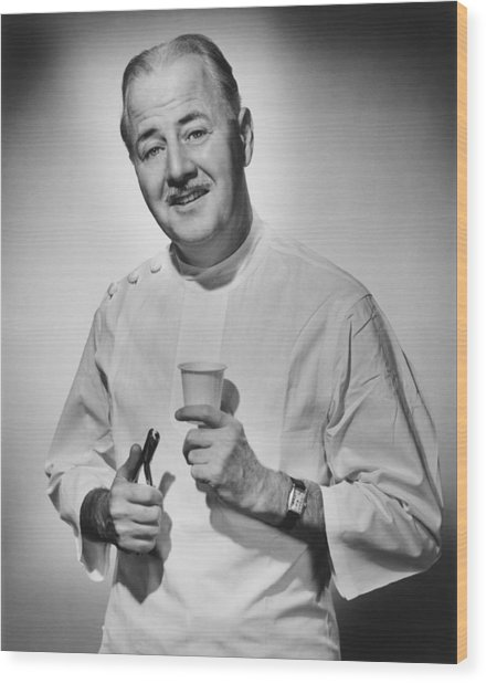 Dentist Holding Pliers And Cup Posing In Studio, (b&w), Portrait Wood Print by George Marks