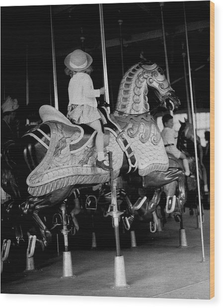 Girl Riding A Carousel Wood Print by George Marks