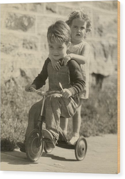 Little Boy Giving Little Girl Ride On Tricycle Wood Print by George Marks