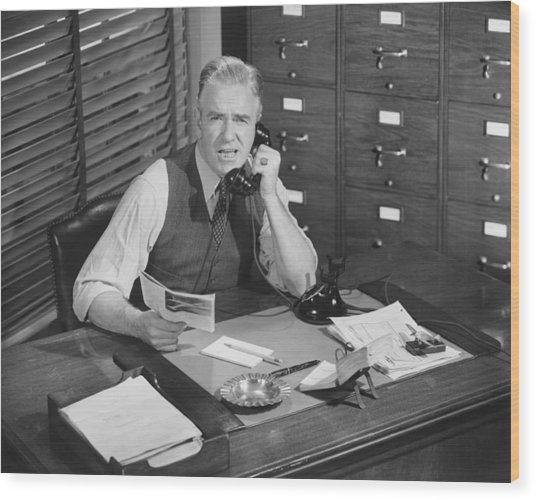 Man Sitting At Desk, Talking On Phone, (b&w), Elevated View Wood Print by George Marks