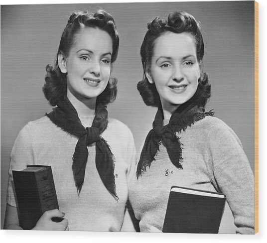 Portrait Of Teenaged Twin Girls Holding Books Wood Print by George Marks