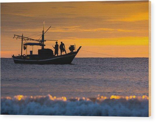 Silhouette Fisherman On Boat In Sunset Huahin Wood Print by Arthit Somsakul