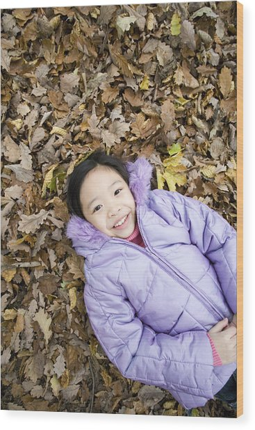 Smiling Girl Lying On Autumn Leaves Wood Print by Ian Boddy