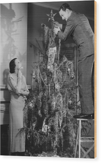 Woman Assisting Man Placing Star On Top Of Christmas Tree, (b&w) Wood Print by George Marks