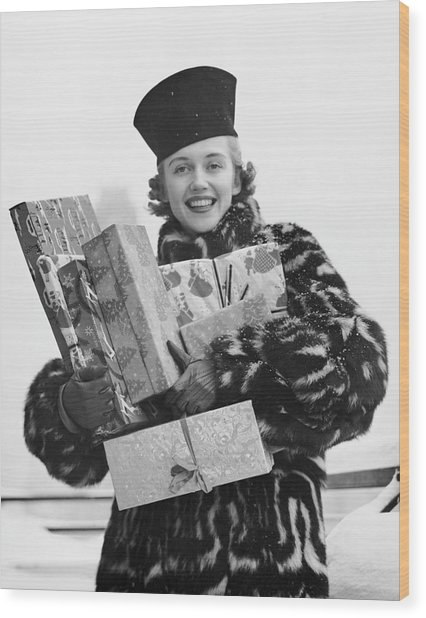 Woman In Fur Coat Holding Christmas Gifts Wood Print by George Marks