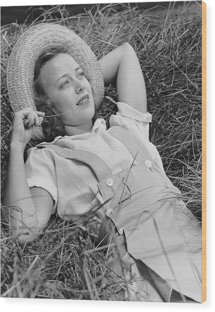 Young Woman Laying In Hay Thinking Wood Print by George Marks