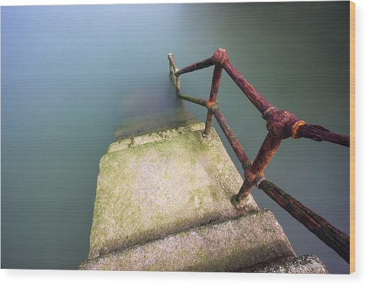 Rusty Handrail Going Down On Water Wood Print