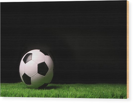 Soccer Ball On Grass Against Black Wood Print